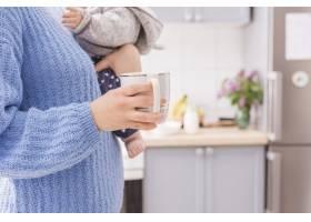 一名男子在厨房里抱着婴儿和杯子_4673638