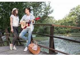 一名男子在桥上给他的女朋友弹吉他_5022772