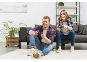 一对年轻夫妇在家中一起玩电子游戏的照片_3882672