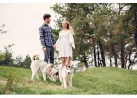 一对美丽的夫妇带着一条狗在夏天的森林里_5007266