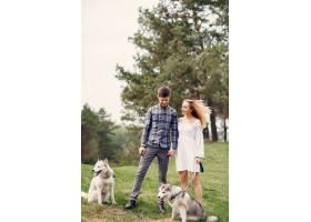 一对美丽的夫妇带着一条狗在夏天的森林里_5007267