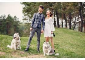 一对美丽的夫妇带着一条狗在夏天的森林里_5007268