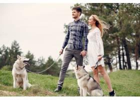 一对美丽的夫妇带着一条狗在夏天的森林里_5007269