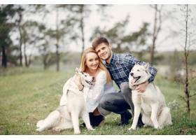 一对美丽的夫妇带着一条狗在夏天的森林里_5007280