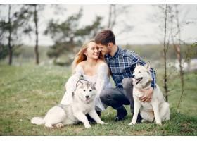 一对美丽的夫妇带着一条狗在夏天的森林里_5007281