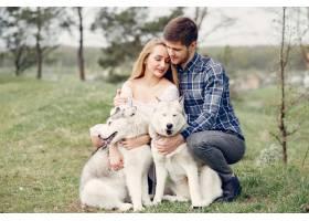 一对美丽的夫妇带着一条狗在夏天的森林里_5007282