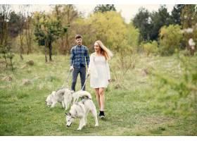 一对美丽的夫妇带着一条狗在夏天的森林里_5007319