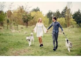 一对美丽的夫妇带着一条狗在夏天的森林里_5007321