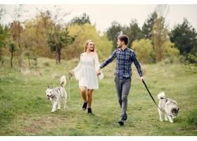 一对美丽的夫妇带着一条狗在夏天的森林里_5007322