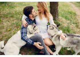 一对美丽的夫妇带着一条狗在夏天的森林里_5007329
