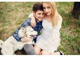 一对美丽的夫妇带着一条狗在夏天的森林里_5007332