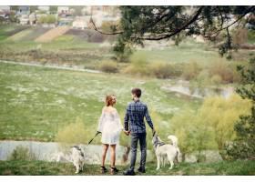 一对美丽的夫妇带着一条狗在夏天的森林里_5007333