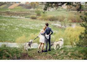 一对美丽的夫妇带着一条狗在夏天的森林里_5007334