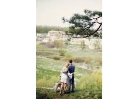 一对美丽的夫妇带着一条狗在夏天的森林里_5007335