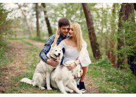 一对美丽的夫妇带着一条狗在夏天的森林里_5007343