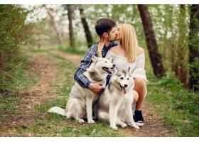 一对美丽的夫妇带着一条狗在夏天的森林里_5007344