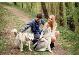 一对美丽的夫妇带着一条狗在夏天的森林里_5007345