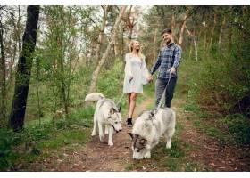 一对美丽的夫妇带着一条狗在夏天的森林里_5011124