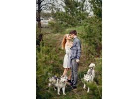 一对美丽的夫妇带着一条狗在夏天的森林里_5011140