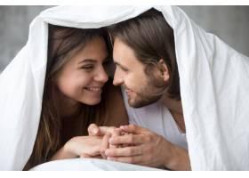 笑容满面的年轻夫妇在床上用毯子盖着玩得很_3938163