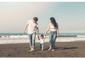 美丽的一家人沿着海滩散步_4380914