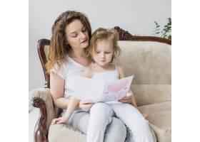 美丽的母女坐在沙发上读母亲节贺卡_4048271