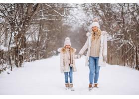母亲和女儿一起在冬季公园散步_3964093