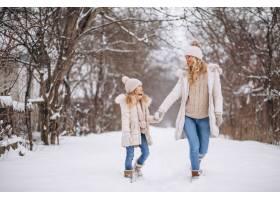 母亲和女儿一起在冬季公园散步_3964094