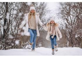 母亲和女儿一起在冬季公园散步_3964105