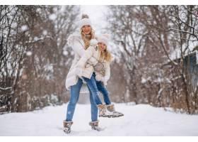 母亲和女儿一起在冬季公园散步_3964106