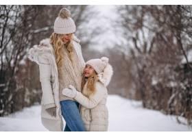 母亲和女儿一起在冬季公园散步_3964107
