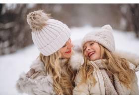 母亲和女儿一起在冬季公园散步_3964108