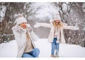 母亲和女儿一起在冬季公园散步_3964109