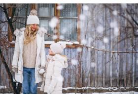 母亲和女儿一起在冬季公园散步_3964110