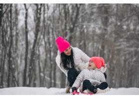 母亲和女儿在冬季公园的盘子上骑车_3962722