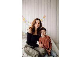 母亲和她的儿子在摄影棚里摆姿势穿着休闲_5073340