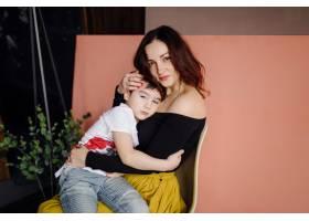 母亲和她的儿子在摄影棚里摆姿势穿着休闲_5073405