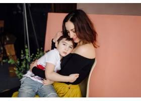 母亲和她的儿子在摄影棚里摆姿势穿着休闲_5073408