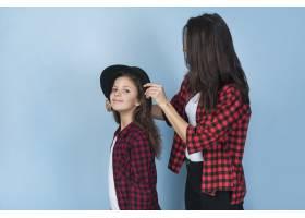 母亲把帽子戴在女儿头上_3957128