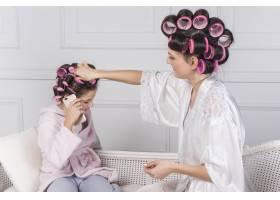 母亲把粉色卷发放在女儿的头发上_3948407