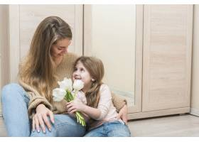 母亲抱着带着白色郁金香花的女儿_3967169