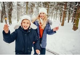 母亲带着可爱的儿子在冬橡树里_4062757