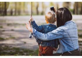 母亲和她的小儿子在公园里玩得很开心_4758294