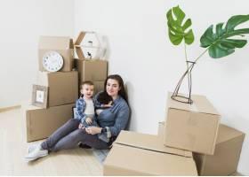 母亲和她的男婴坐在新家的纸箱里的肖像_3957200