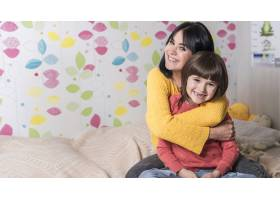 母亲在床上从后面拥抱小女儿_3979035