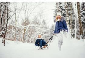 母亲带着可爱的儿子在冬橡树里_4062732