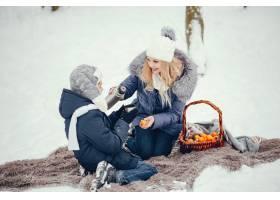 母亲带着可爱的儿子在冬橡树里_4062738