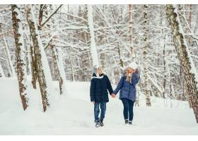 母亲带着可爱的儿子在冬橡树里_4062746