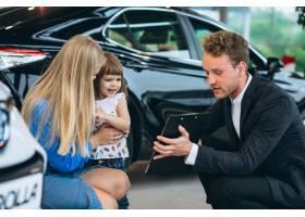 母女在汽车展厅与销售人员交谈_5157733