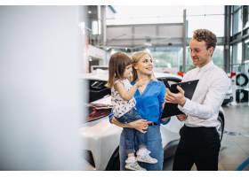 母女在汽车展厅与销售人员交谈_5157793